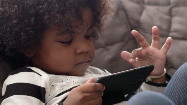 vidéos et rushes de garçon noir jouant le jeu de smartphone sur le sofa, les images malsaines de addiction.slow motion de gadget. - résolution 4k