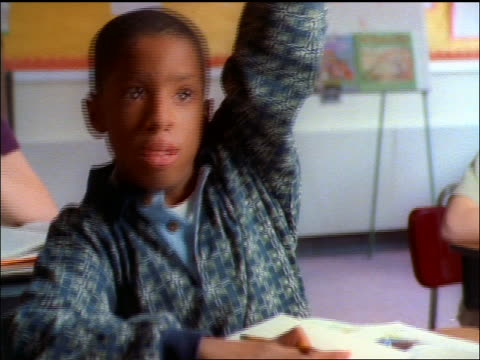 black boy sitting at desk raising hand in classroom + talking - solo un bambino maschio video stock e b–roll