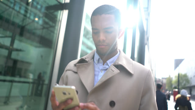 Black business man outdoors texting on his smartphone