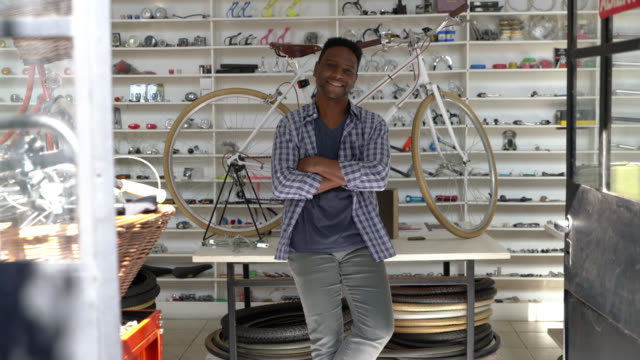 Black business owner at his bicycle repair shop sitting on the table with arms crossed looking at the camera smiling