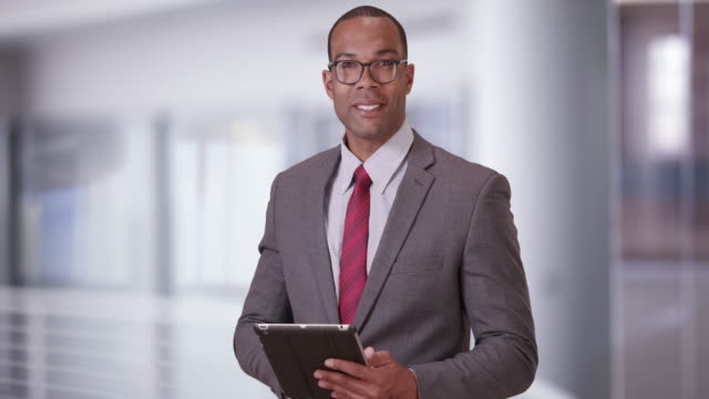 a black business professional poses for a portrait with his tablet and glasses - ladder of success stock videos & royalty-free footage