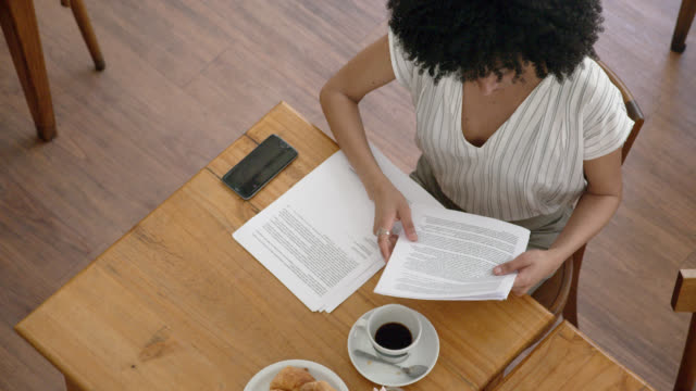 black business woman checking some documents while drinking coffee and eating croissants at a coffee shop - coffee variation stock videos & royalty-free footage