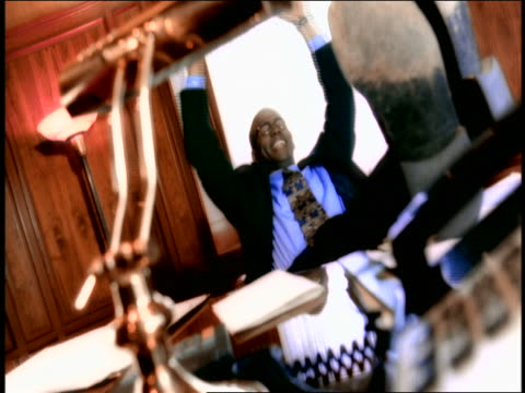 stockvideo's en b-roll-footage met canted black businessman with feet on desk yawning, stretching, relaxing + loosening tie - 1998