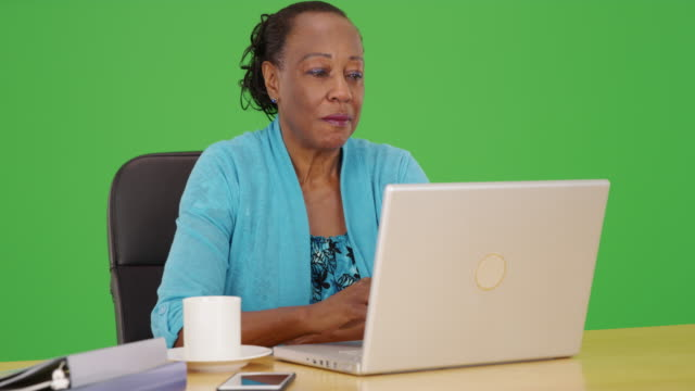 a black businesswoman happily uses her laptop at her desk on green screen - maestra video stock e b–roll