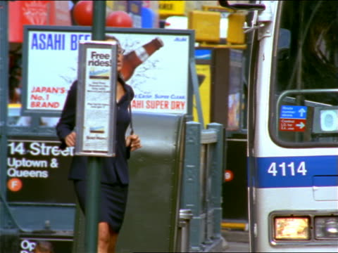 Black businesswoman in suit running towards bus + missing it on NYC street / checks watch