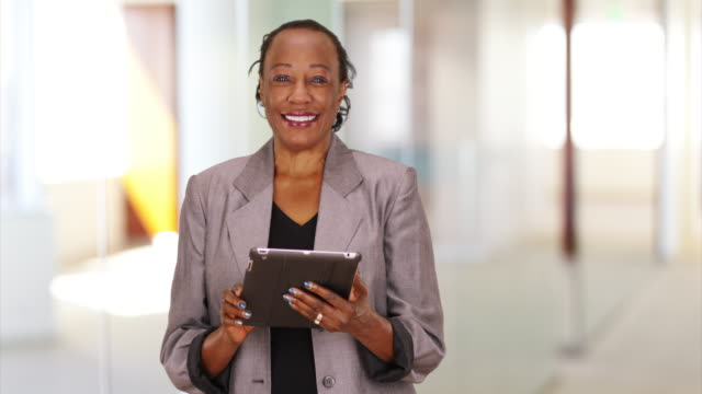 a black businesswoman laughs while using her tablet - ワーキングシニア点の映像素材/bロール