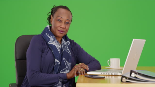 a black businesswoman poses for a portrait at her desk on green screen - maestra video stock e b–roll
