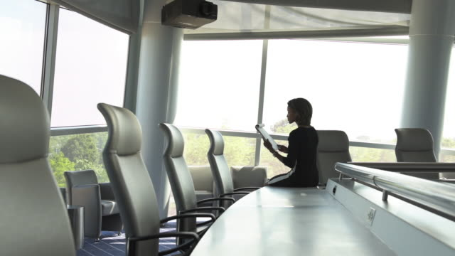 Black businesswoman reading notepad in spacious conference room