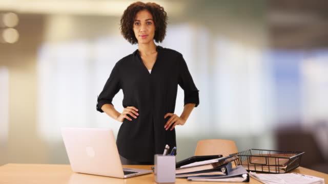 vídeos de stock, filmes e b-roll de black businesswoman standing behind office desk looking confident.  professional woman hands on waist with serious attitude. - trabalhadora de colarinho branco