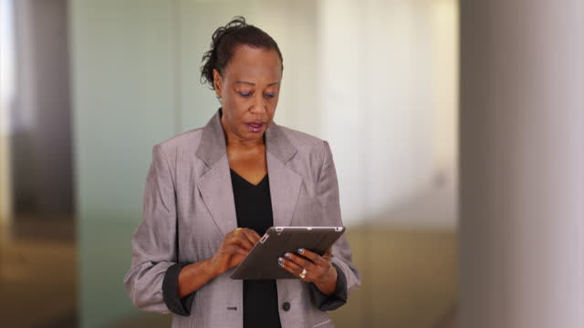 a black businesswoman using a tablet computer in her office - ワーキングシニア点の映像素材/bロール
