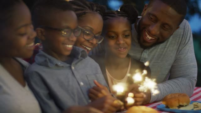 Black Canadian Family Sitting Together with Sparklers