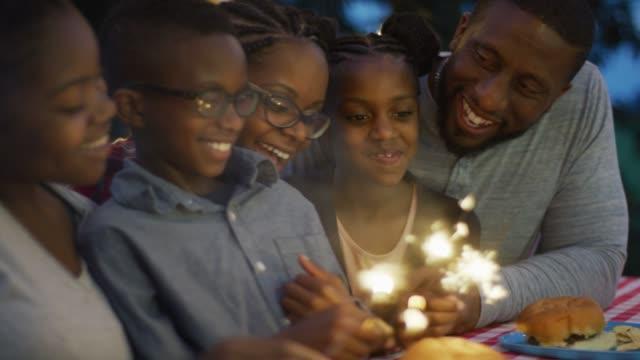 Famille canadienne noire assis avec feux de Bengale