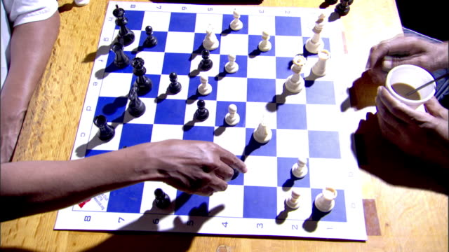 black captured chess game pieces sitting behind board black male arm w/ hand resting on shirt sleeve upper arm. - sleeve stock videos & royalty-free footage