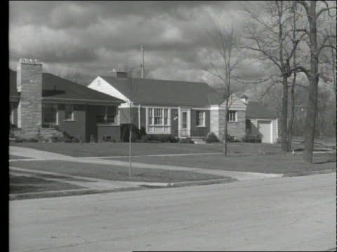 b/w 1949 black car driving past suburban houses - 1949 stock-videos und b-roll-filmmaterial