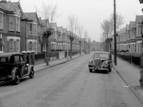 a black car moves off along a typical suburban street 1957 - doppelhaus stock-videos und b-roll-filmmaterial