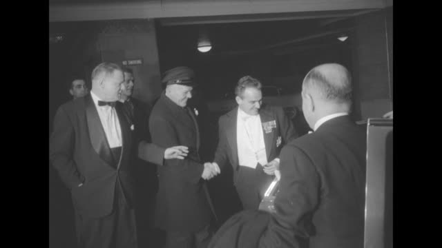 Black car pulls up outside Waldorf Astoria doorman opens car door and Rainier III of Monaco gets out shakes hands while he waits for Grace Kelly to...
