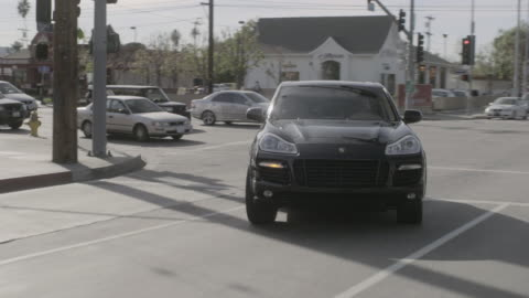 rear pov black car turning right and driving on city streets with traffic / los angeles, california, united states - vorderansicht stock-videos und b-roll-filmmaterial