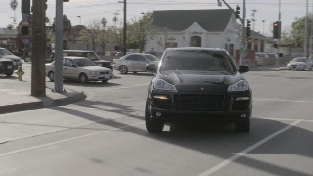 rear pov black car turning right and driving on city streets with traffic / los angeles, california, united states - sports utility vehicle stock-videos und b-roll-filmmaterial