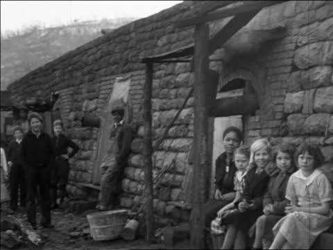 black caucasian families sitting in front of coke ovens / pennsylvania / news - 1935年点の映像素材/bロール