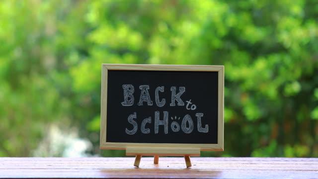 """vidéos et rushes de tableau noir avec le mot écrit """"retour à l'école"""" concept. - gomme"""