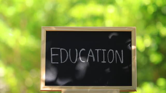 「教育」という言葉の概念を持つ黒い黒板。 - 消しゴム点の映像素材/bロール