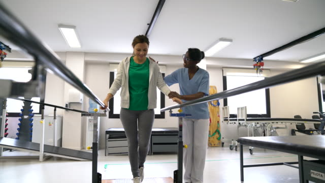 black cheerful therapist motivating female patient walk with the help of parallel bars - physiotherapy stock videos & royalty-free footage