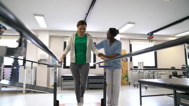stockvideo's en b-roll-footage met zwarte vrolijke therapeut motiverend vrouwelijke patiënt lopen met behulp van parallelle staven - fysiotherapie