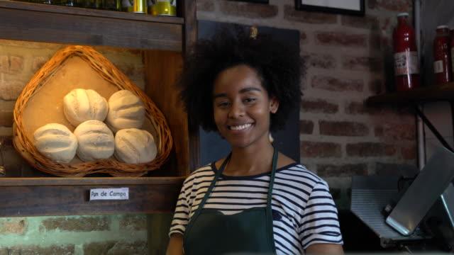 vídeos de stock, filmes e b-roll de mulher jovem negra e alegre em uma padaria sorrindo para a câmera - feirante