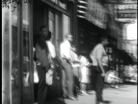 vidéos et rushes de black citizens stand on a street corner in newark's slums. - new jersey