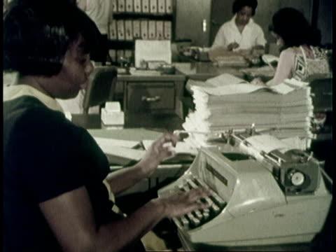 1970 ms black clerk typing / united states - 1970 stock-videos und b-roll-filmmaterial
