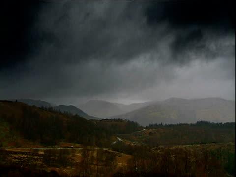 Black clouds billow over hills of Trossacks National Park Scotland