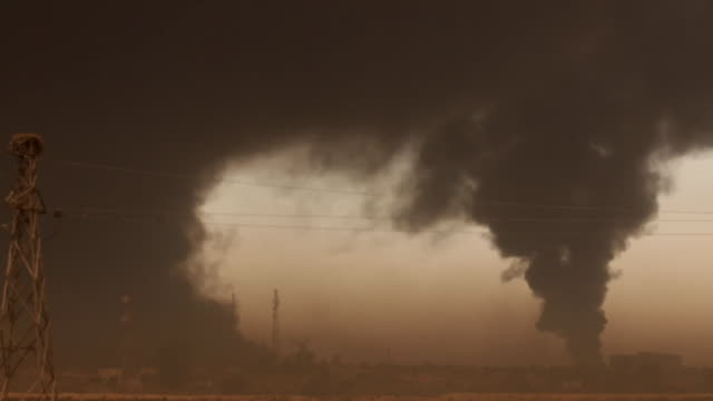 black clouds cover the skies of mosul after retreating islamic state fighters set fire to oil wells - 武力攻撃点の映像素材/bロール