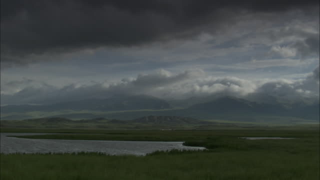 Black clouds over hills and lake, Bayanbulak grasslands.