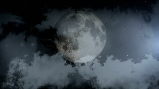 black clouds passing in front of the moon in the night sky - full moon stock videos & royalty-free footage