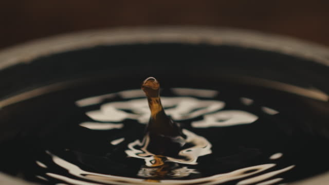 black coffee drop falling at factory - coffee drink stock videos & royalty-free footage