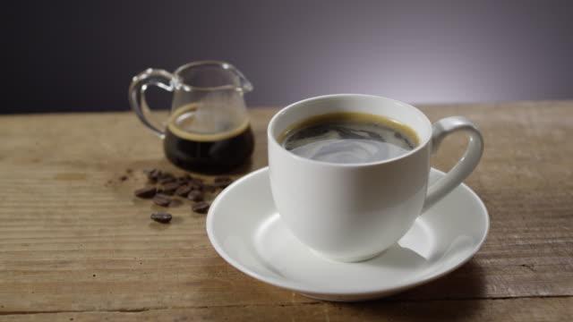 vídeos de stock, filmes e b-roll de black coffee on wooden table - molécula de cafeína