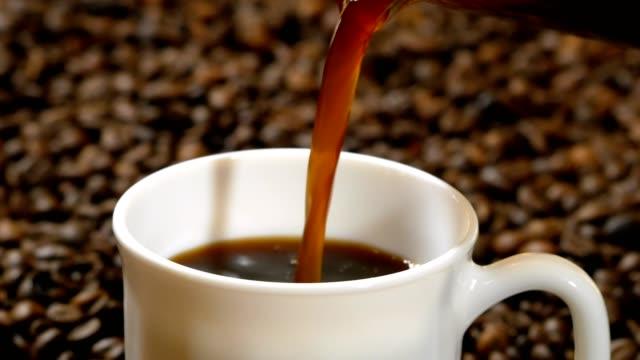 zwarte koffie gieten in witte kop op stapel van geroosterde koffiebonen