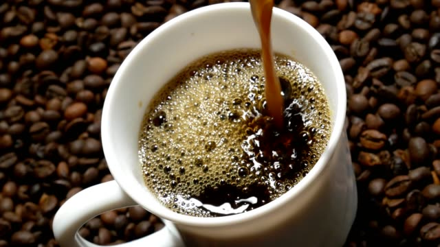 black coffee pouring into white cup on pile of roasted coffee beans - mug stock videos and b-roll footage