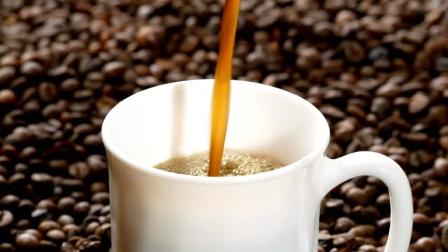 black coffee pouring into white cup on pile of roasted coffee beans - kitchenware department stock videos and b-roll footage
