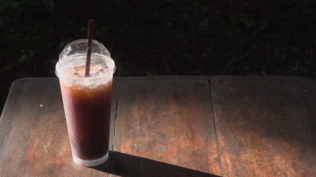 black coffee with ice in sunlight - straw stock videos & royalty-free footage