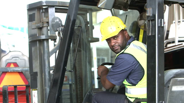 black construction worker climbing onto forklift - forklift truck stock videos and b-roll footage