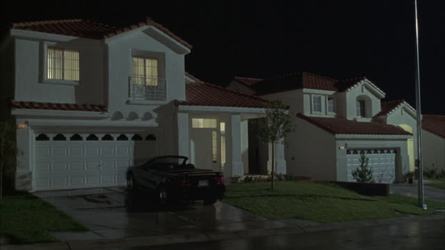 A black convertible car is parked in the driveway of a Spanish style suburban home at night.