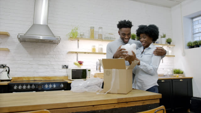 black couple at home unpacking their piggybank with their savings and looking very happy - mail stock videos & royalty-free footage