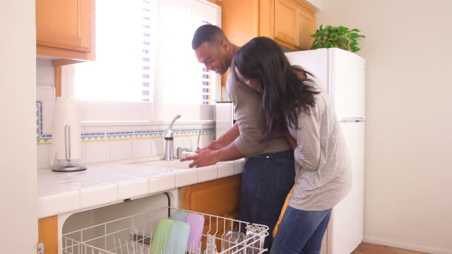 black couple being silly while doing the dishes - dreiviertelansicht stock-videos und b-roll-filmmaterial