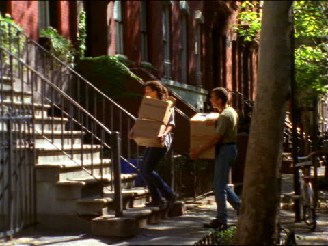 vídeos de stock e filmes b-roll de pan black couple carrying boxes from car up front steps of brownstone / brooklyn, nyc - degraus