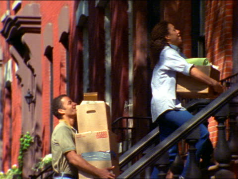 pan black couple carrying boxes up front steps of brownstone / brooklyn, nyc - front stoop stock videos and b-roll footage
