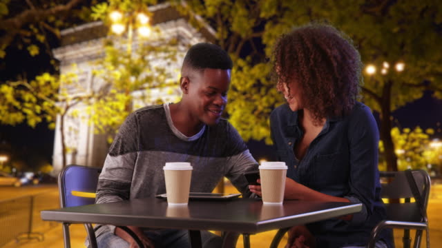 Black couple enjoys evening in Paris, chatting and using smartphone