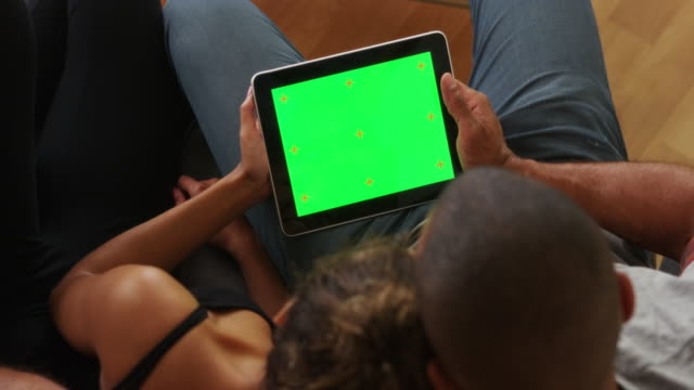 Black couple holding tablet with greenscreen