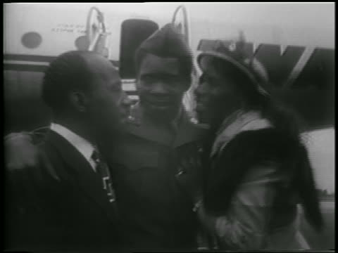 black couple hugging + kissing soldier at airport / korean war pow's homecoming - mid adult couple stock videos & royalty-free footage