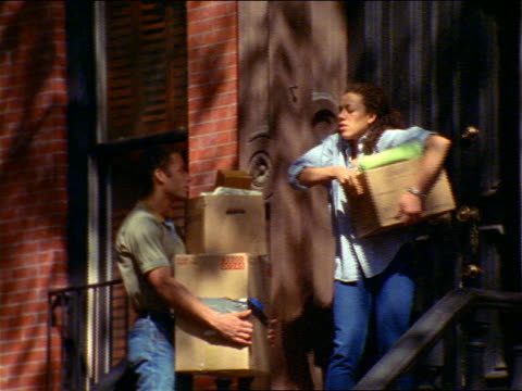 Black couple moving into brownstone / woman puts box on man to unlock door / Brooklyn, NYC